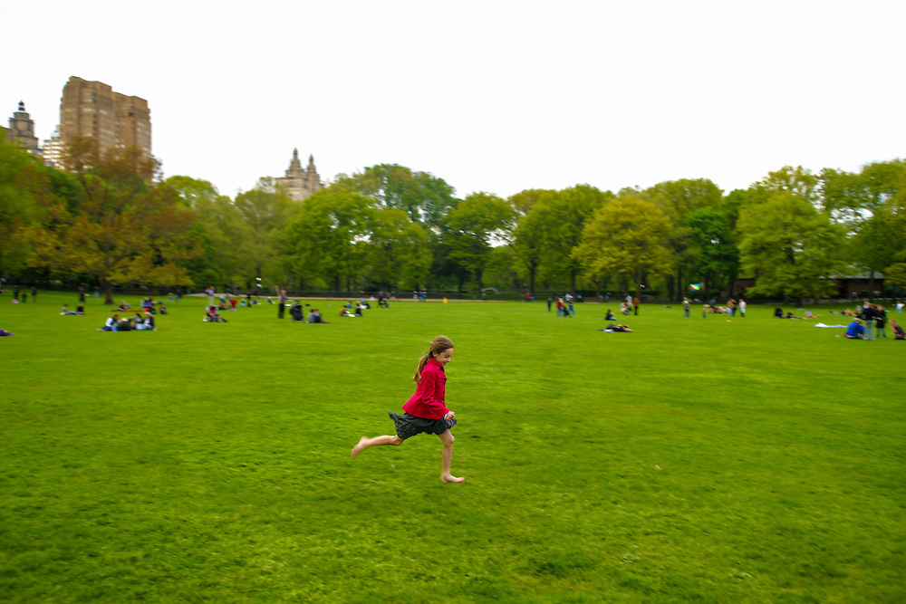 A young girl runs on the grass in Central Park, in New York.
