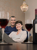 Smiling couple sitting at table in living room wine glasses on foreground (portrait)