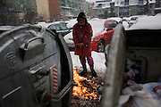 Prishtina neighborhood of Dardania. Roma woman with a fire...Large snow storms in Kosovo, 2/19/09.