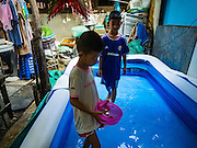 08 APRIL 2016 - BANGKOK, THAILAND:   Boys play in an inflatable splash pool in front of their homes in Mahakan Fort. The community is known for fireworks, fighting cocks and bird cages. Mahakan Fort was built in 1783 during the reign of Siamese King Rama I. It was one of 14 fortresses designed to protect Bangkok from foreign invaders, and only of two remaining, the others have been torn down. A community developed in the fort when people started building houses and moving into it during the reign of King Rama V (1868-1910). The land was expropriated by Bangkok city government in 1992, but the people living in the fort refused to move. In 2004 courts ruled against the residents and said the city could take the land. The final eviction notices were posted last week and the residents given until April 30 to move out. After that their homes, some of which are nearly 200 years old, will be destroyed.   PHOTO BY JACK KURTZ