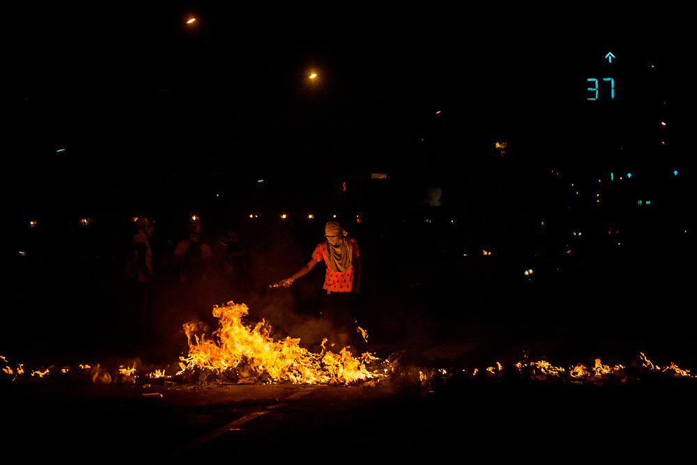 CARACAS, VENEZUELA - MAY 20, 2017:  Anti-government protesters man a road block between clashes with security forces at night.  The streets of Caracas and other cities across Venezuela have been filled with tens of thousands of demonstrators for nearly 100 days of massive protests, held sincde April 1st. Protesters are enraged at the government for becoming an increasingly repressive, authoritarian regime that has delayed elections, used armed government loyalist to threaten dissidents, called for the Constitution to be re-written to favor them, jailed and tortured protesters and members of the political opposition, and whose corruption and failed economic policy has caused the current economic crisis that has led to widespread food and medicine shortages across the country.  Independent local media report nearly 100 people have been killed during protests and protest-related riots and looting.  The government currently only officially reports 75 deaths.  Over 2,000 people have been injured, and over 3,000 protesters have been detained by authorities.  PHOTO: Meridith Kohut