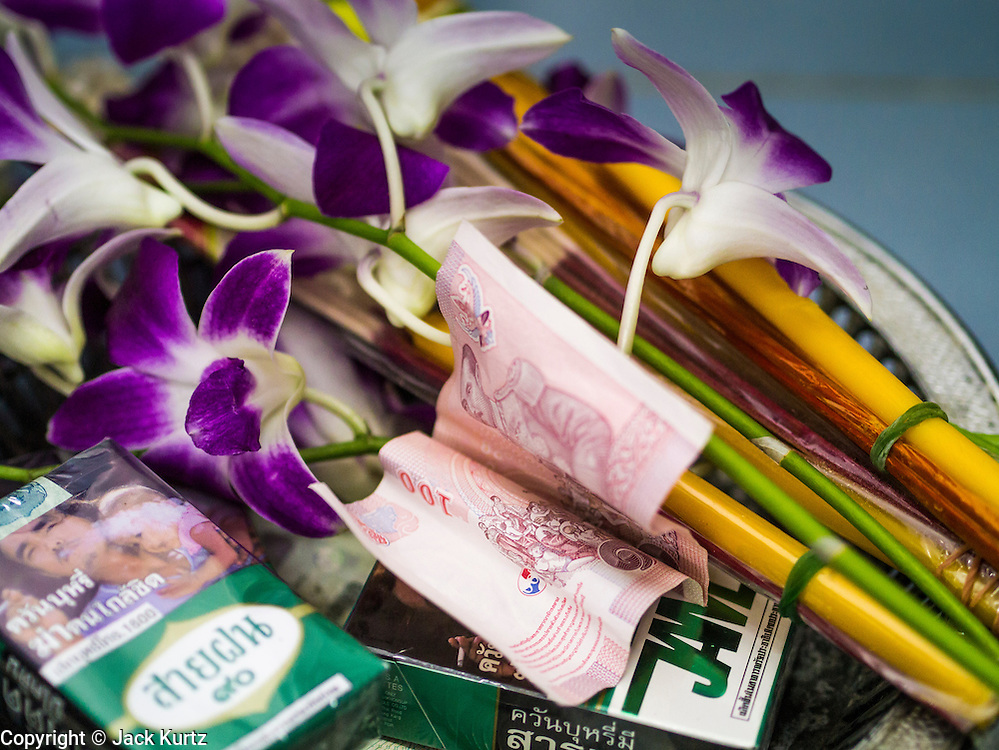 """23 MARCH 2013 - NAKHON CHAI SI, NAKHON PATHOM, THAILAND:  A 100 Baht note (about $3.30 US), orchids and cigarettes donated to a monk for a Sak Yant tattoo at Wat Bang Phra. Wat Bang Phra is the best known """"Sak Yant"""" tattoo temple in Thailand. It's located in Nakhon Pathom province, about 40 miles from Bangkok. The tattoos are given with hollow stainless steel needles and are thought to possess magical powers of protection. The tattoos, which are given by Buddhist monks, are popular with soldiers, policeman and gangsters, people who generally live in harm's way. The tattoo must be activated to remain powerful and the annual Wai Khru Ceremony (tattoo festival) at the temple draws thousands of devotees who come to the temple to activate or renew the tattoos. People go into trance like states and then assume the personality of their tattoo, so people with tiger tattoos assume the personality of a tiger, people with monkey tattoos take on the personality of a monkey and so on. In recent years the tattoo festival has become popular with tourists who make the trip to Nakorn Pathom province to see a side of """"exotic"""" Thailand. The 2013 tattoo festival was on March 23.  PHOTO BY JACK KURTZ"""