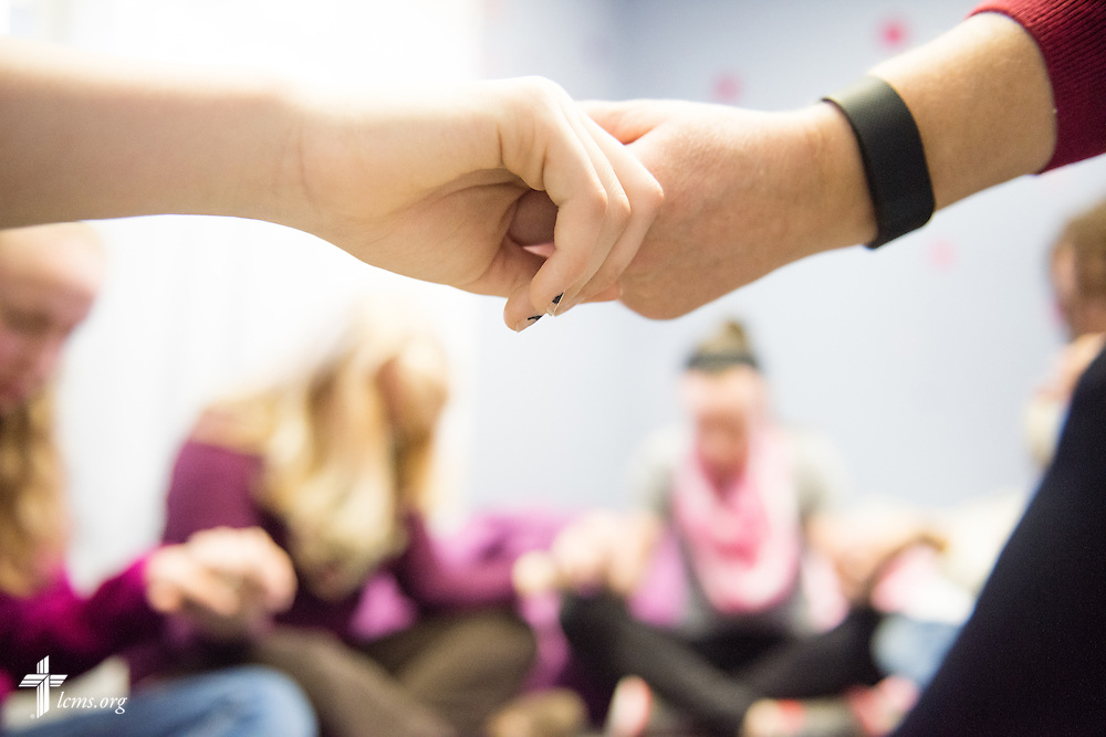 A group of young women and group leaders hold hands for prayer during a small group session following worship  at Brookfield Lutheran Church on Sunday, March 29, 2015, in Brookfield, Wis. LCMS Communications/Erik M. Lunsford