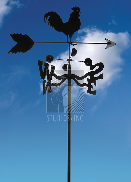 black iron weather vane against blue sky with clouds