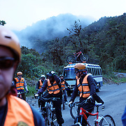 "Mountain Biking on Death Road, Bolivia...A tour group of Mountain Bikers stop to rest and be briefed about the next stage of the journey by their tour leader, biking down infamous narrow dirt road, most of the road no wider than 3.2 meter's, is cut into the side of the mountain with sheer drops to the left of up to 600 meter's with virtually no safety rails on the winding steep decent....The North Yugas Road is a 64 Kilometer road leading from La Paz to Corioico. It is legendary for it's extreme danger and in 1995 the Inter American Development Bank christened is as the ""world's most dangerous road"".. The road was built in the 1930's during the Chaco War by Paraguayan prisoners to connect the Amazon rainforest region of Northern Bolivia to it's capital City La Paz. One estimate is that 200 to 300 travelers were killed yearly along the road. On 24 July 1983, a bus veered off the Yungas Road and into a canyon, killing more than 100 passengers in what is said to be Bolivia's worst road accident..A new stretch of the La Paz-Coroico highroad was opened in 2006 to bypass the notorious stretch known as death road..The danger of the road has now made it a popular tourist destination starting in the 1990's and drawing thrill-seekers and mountain bike enthusiasts who ride on the 64km mainly downhill stretch from La Cumbre, a 4,700 meter peak to Yolosa, a decent of 3600 meter's (11,800 feet). The journey includes breathtaking views of snow covered peaks and towering cliffs and starts along modern asphalted road before entering the jungle itself and the most dangerous and notorious part of the ride. The infamous narrow dirt road, most of the road no wider than 3.2 meter's, is cut into the side of the mountain with sheer drops to the left of up to 600 meter's with virtually no safety rails on the winding steep decent..There are now many tour operators catering to this activity, providing information, guides, transport and equipment. Nevertheless, the Yungas Road remains dangerou"