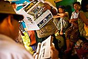 Fahrgaeste Lesen im Zug. Die Circle Line ist ein Zug der die verschiedenen Vororte Yangons mitteinander verbindet. Eine Rundfahrt von der Yangon Railway station dauert etwa 3 Stunden, mit zahlreichen Zwischenstops. Teilweise werden ganze Maerkte transportiert. Yangon, Myanmar, 14ter Mai 2013.