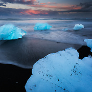 Sunset highlights the unique shape, texture, and colors of the icebergs found on the black sand shores of the Jökulsárlón lagoon in Skaftafell National Park.