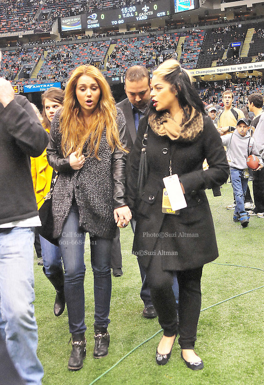 Actor and singer Miley Cyrus and her friend walk off the field before kick off. hangs out on the Saints sidelines and poses with Saints owner Rita Benson Leblanc prior to the kick off against the St. Louis Rams.The New Orleans Saints play the St. Louis Rams in New Orleans at the Super Dome Sunday Dec. 12,2010.  Saints were winning 21-6 at half time.Photo©SuziAltman.