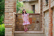A young girl laughing at a villa in Tuscany.