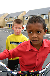 Boys playing on bicycle on Housing Association estate; Halifax; Yorkshire UK