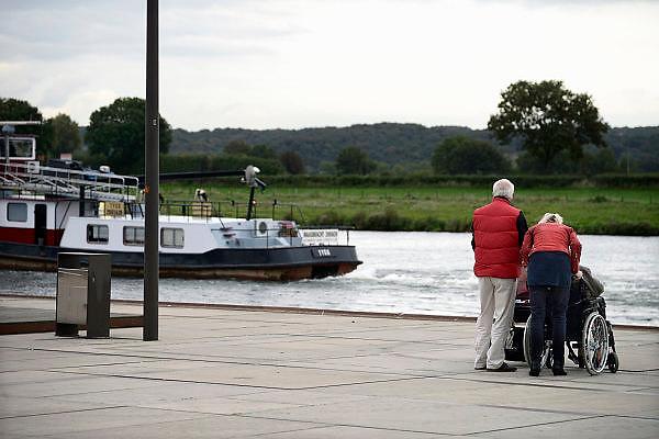 Nederland, Cuijk, 9-10-2013Een oudere man en wat jongere vrouw, vader en dochter misschien, staan op de maaskade naar de rivier en de scheepvaart te kijken. De man, opa, heeft een kinderwagen en de vrouw een rolstoel waar een hoogbejaarde vrouw in zit.Foto: Flip Franssen/Hollandse Hoogte