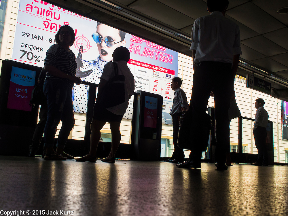 02 FEBRUARY 2015 - BANGKOK, THAILAND: People wait for the BTS Skytrain in Siam Station in central Bangkok. Government sources are saying that security has been heightened following two small bomb attacks at a city office in the station, which is next to Siam Paragon, an upscale mall. One person received minor injuries in the attack and a couple of windows were blown out. After months of relative calm following the May 2014 coup, tensions are increasing in Bangkok. The military backed junta has threatened to crack down on anyone who opposes the government. Relations with the United States have deteriorated after Daniel Russel, the US Assistant Secretary of State for Asian and Pacific Affairs, said that normalization of relations between Thailand and the US would depend on the restoration of a credible democratically elected government in Thailand.       PHOTO BY JACK KURTZ