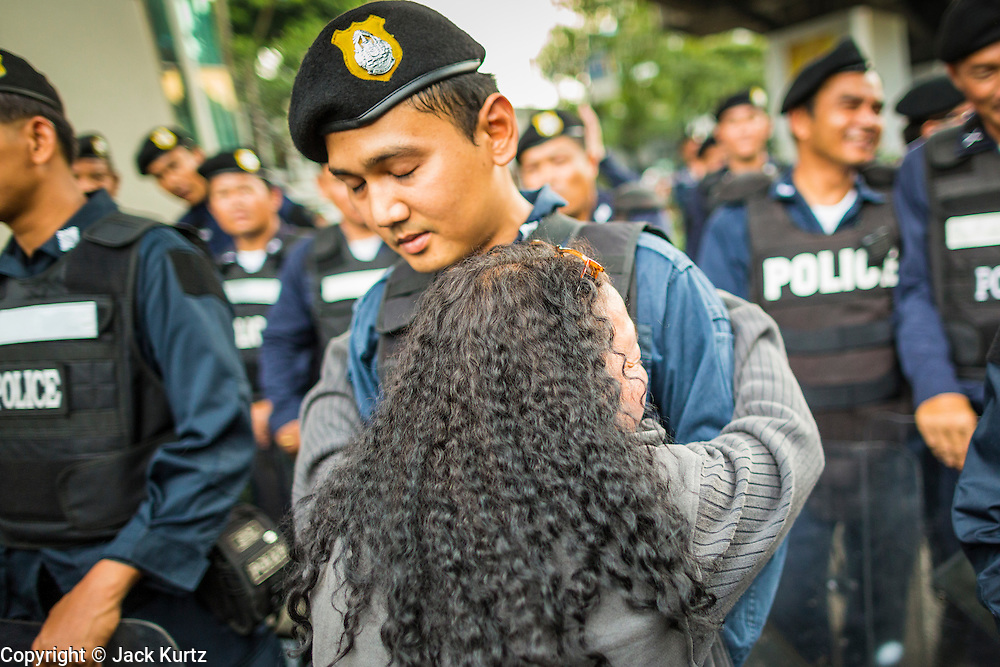 26 MAY 2014 - BANGKOK, THAILAND: A woman hugs riot police during a protest against the coup in Thailand at Victory Monument during a pro-democracy rally in Bangkok. About two thousand people protested against the coup in Bangkok. It was the third straight day of large pro-democracy rallies in the Thai capital as the army continued to tighten its grip on Thai life.   PHOTO BY JACK KURTZ