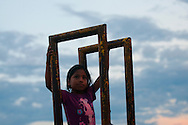 A young girl climbs the stairs of a slide at a playground on the edge of the Amazon River in Iquitos, Peru.