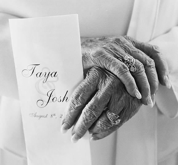 grandmas fingers holding a wedding invitation. long fingers large diamond ring and dainty wrinkled aged hands.