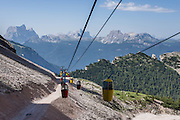 From Gondellift Forcella Staunies, see Monte Pelmo, Monte Civetta, and Croda da Lago (left to right) on the horizon to the southwest. A lift to Forcella Staunies on Monte Cristallo gives unforgettable views over the Dolomites mountains near Cortina d'Ampezzo, in the Province of Belluno, Veneto region, Italy, Europe. Monte Cristallo lies within Parco Naturale delle Dolomiti d'Ampezzo. Directions: From Cortina, drive 6km east on SR48 to the large parking lot for Ski Area Faloria Cristallo Mietres (just west of Passo Tre Croci Federavecchia). Take a chair-lift from Rio Gere to Son Forca (rising from 1698m to 2215m). Then ride the old style ovovia (egg-shaped) Gondellift Forcella Staunies to Rifugio Guido Lorenzi (2932m) for astounding views. Climbers enjoy spectacular via ferrata routes here. The ski resort of Cortina d'Ampezzo (Ladin: Anpëz, German: Hayden, at 1224 meters/4016 feet) is surrounded by the beautiful Dolomiti, part of the Southern Limestone Alps. Cortina gained worldwide fame after hosting the 1956 Winter Olympics. UNESCO honored the Dolomites as a natural World Heritage Site in 2009.