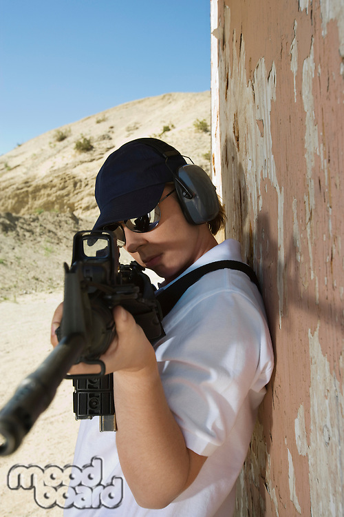 Woman aiming machine gun at firing range