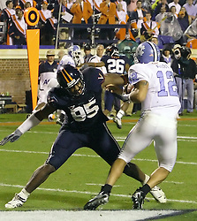 UVA's Jeffery Fitzgerald (95) forces UNC's QB Joe Daley (12) to scramble from his own end zone.  Daley replaced starting QB Cam Sexton in the second half as UVA shutdown the Tarheels 23-0 at Scott Stadium in Charlottesille, VA on Thursday, October 19, 2006.