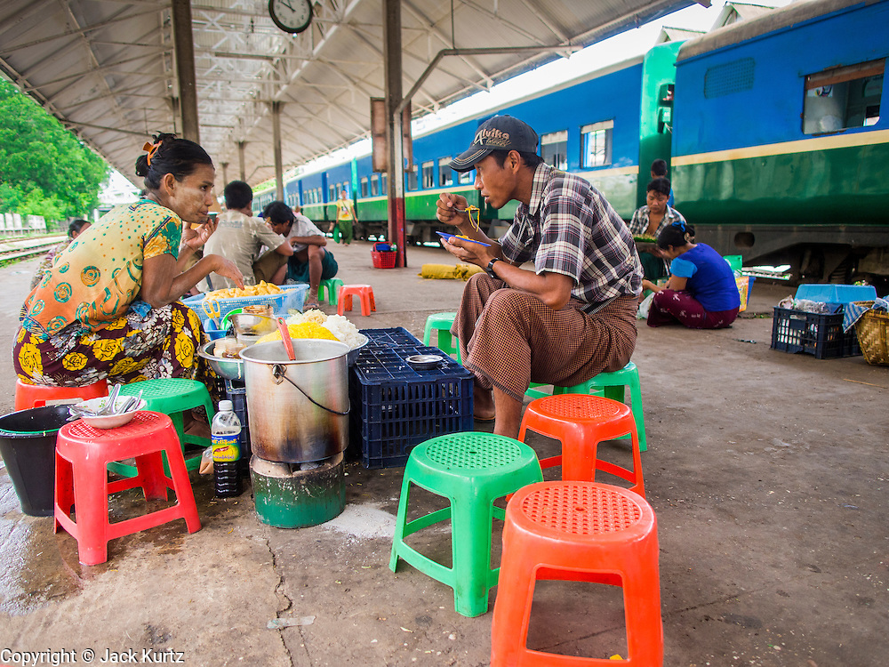 """05 JUNE 2014 - YANGON, YANGON REGION, MYANMAR: People eat lunch in the Yangon train station while they wait for the """"circular train"""" to come into the station. The Yangon Circular Train is a commuter train that circles Yangon, Myanmar (Rangoon, Burma). The train is 45 kilometers long, makes 38 stops and takes about three hours to make a loop of the city.     PHOTO BY JACK KURTZ"""