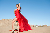 Full length of a young woman wrapped in red cloth on arid landscape