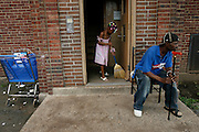 A young girl sweeps the entrance to the public housing project building she shares with her father.
