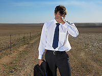 Businessman holding his head in the middle of nowhere