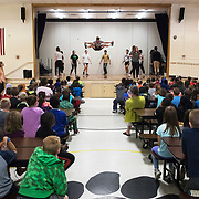 "Matt Golden '20 of New Bedford, Mass., perform a high jump center stage while performing with Bates students in Gretchen Berg's short term course ""Teach, Tour, Perform"" while performing for McMahon Elementary School third graders on May 24, 2018. ""Teach, Tour, Perform, is aimed at the curriculum of what teachers are actually teaching in 3rd grade science so it's really cool, says Berg."""