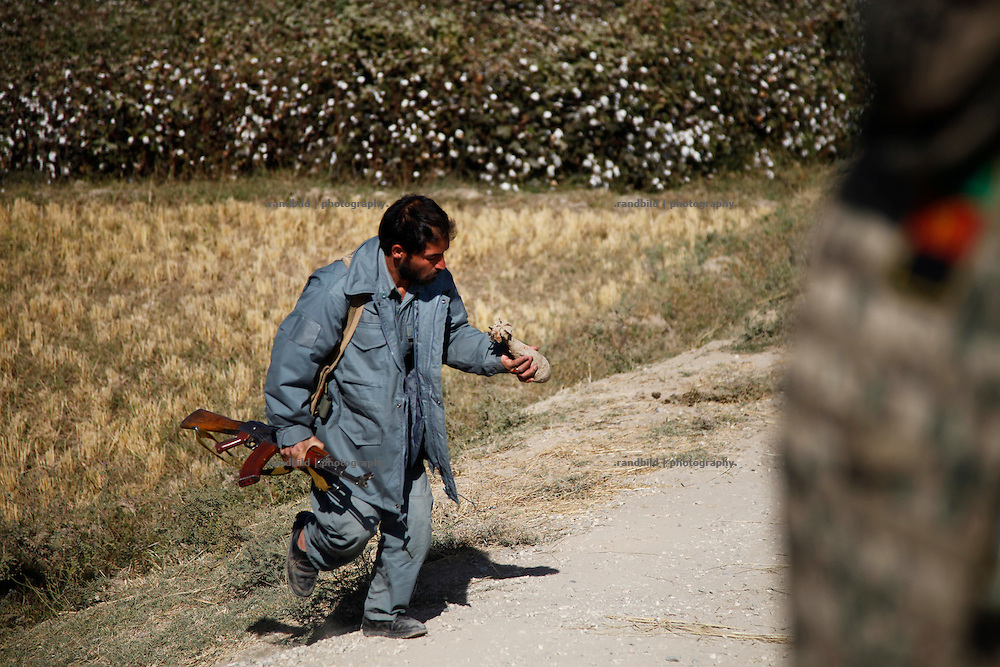 An afghan police man clears an old rusty mortar grenade found beside the road by german patrol.