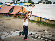 05 AUGUST 2015 - KATHMANDU, NEPAL:   A boy tries to fly a kite in a large Internal Displaced Person (IDP) Camp in the center of Kathmandu. The camp is next to one the most expensive international hotels in Kathmandu. More than 7,100 people displaced by the Nepal earthquake in April live in 1,800 tents spread across the space of three football fields. There is no electricity in the camp. International NGOs provide water and dug latrines on the edge of the camp but the domestic waste water, from people doing laundry or dishes, runs between the tents. Most of the ground in the camp is muddy from the running water and frequent rain. Most of the camp's residents come from the mountains in northern Nepal, 8 - 12 hours from Kathmandu. The residents don't get rations or food assistance so every day many of them walk the streets of Kathmandu looking for day work.      PHOTO BY JACK KURTZ