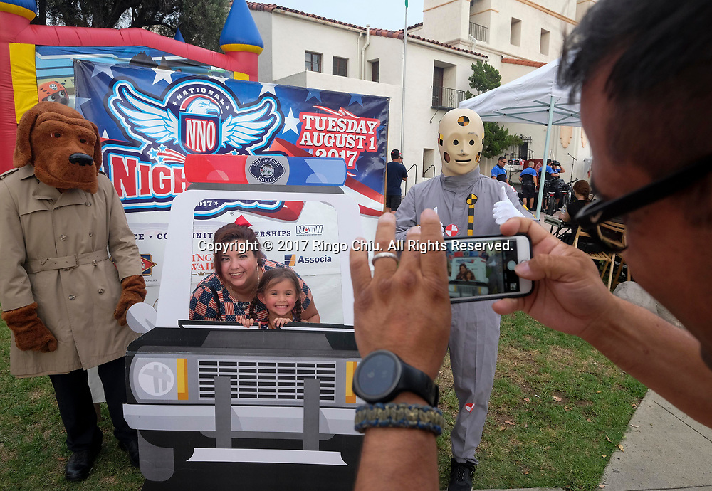 Participants take photos during National Night Out in San Gabriel, California, on Tuesday, Aug. 1, 2017. National Night Out is a community-police awareness-raising event in the United States and Canada, held the first Tuesday of August. Texas and Florida have the option to use the alternate date of the first Tuesday in October to avoid hot weather.(Photo by Ringo Chiu)<br /> <br /> Usage Notes: This content is intended for editorial use only. For other uses, additional clearances may be required.