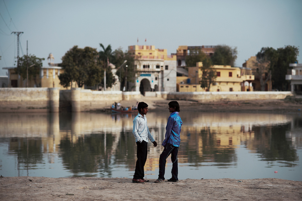 Boys stand together looking across the water at Sadhu Bela, a Hindu temple on the Indus River, Sukkur, Sindh province, Pakistan on March 23, 2012. A rise in in reports of forced conversion of Hindu girls to Islam in provinces in Pakistan has gained prominence within the political, media, religious and social domains with the case of a 21 year old woman Rinkle Kumari. On February 24, 2012 her family reported to police of Ghotki district, Sindh province that she had been abducted by armed men from the family home in the village of Mirpur Mathelo. it is then alleged by the family and broadrer hindu community that she was forced to convert to Islam and marry Syed Naveed Shah, a neighbour of the girl within their village. Complications with court hearings for the case, perceptions by the Muslim community that the police sided with the Muslim community when dealing with issue and the politicisation of the case by a Pakistan Peoples Party Member for National Assembly Mian Abdul Haq alias Mian Mitho has led to a hearing being called in the Supreme Court, Islamabad, Pakistan on March 26, 2012. The hearing will hopefully ascertain whether the girl was abducted or in fact left with Syed Naveed Shah of her own free will.