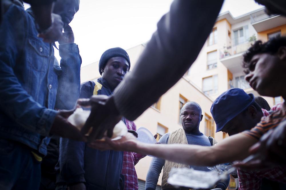 Alcuni migranti aspettano di ricevere il pasto. Nelle ex palazzine olimpiche lavorano a titolo gratuito alcune associazioni e volontari che forniscono cibo e beni di prima necessità.