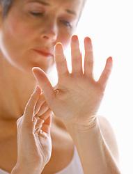 Mature Woman Massaging Hands
