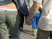 close up of young couple walking hand in hand over the Brooklyn Bridge