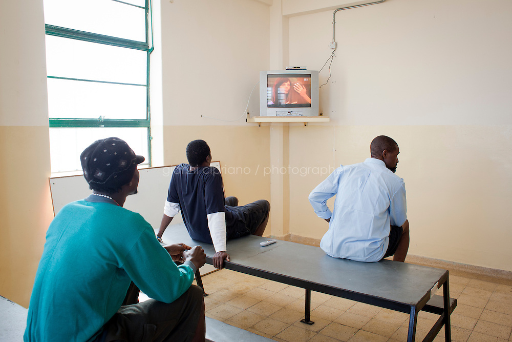 HAL FAR, MALTA - JUNE 20: Sub-saharan immigrants that arrived from Libya watch an Italian TV channel at the Lyster Barracks Closed Center, a detention center for immigrants in Hal Far (which translates as Rats' town), Malta, on June 20, 2011. All immigrants who enter in Malta illegally are detained. Upon arrival to Malta, irregular migrants and asylum seekers are sent to one of three dedicated immigration detention facilities: the Lyster Barracks Closed Centre, the Safi Closed Centre, and the Ta'kandja Closed Centre. Once apprehended by the authorities, immigrants remain in detention even after they apply for refugee status. detention lasts as long as it takes for asylum claims to be determined. This usually takes months; asylum seekers often wait five to 10 months for their first interview with the Refugee Commissioner. Asylum seekers may be detained for up to 12 months: at this point, if their claim is still pending, they are released and transferred to an Open Center.