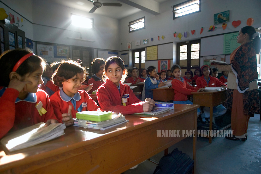 Students listen during classes at St. Teresa's Girls School, November 15, 2005, Rawalpindi, Pakistan. St. Teresa's is one of the few co-religious schools in Pakistan where both Christian and Muslim students attend classes together. The school is run by Chrisitian nuns who select students from poor families who would otherwise not be able to afford their children an education. Female education in Pakistan is lacking, where literacy rates amongst women are as low as 30% in urban areas, and even lower in rural regions. Girls are often kept out of school and work at home where they will be forced into an arranged marriage. (Photo by Warrick Page)