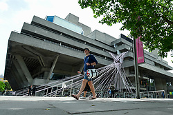 © Licensed to London News Pictures. 03/07/2020. LONDON, UK. A couple passes pink tape wrapped around the National Theatre on the South Bank as part of the #MissingLiveTheatre initiative, a project by theatre designers Scene Change to support those in the live theatre industry through Covid-19 and to help theatres bring shows back into production.  So far, 50 theatres across the UK have signed up to the initiative.  Theatres are remain closed even though the UK government has relaxed certain coronavirus pandemic lockdown restrictions allowing other businesses to reopen.  Photo credit: Stephen Chung/LNP