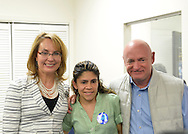 Garden City, New York, USA. April 17, 2016. L-R, GABBY GIFFORDS, former United States Congresswoman; volunteer AURA OSORIO of Bellrose; and Gifford's husband MARK KELLY, former NASA astronaut, pose for a photograph after Giffords and Kelly spoke about the importance of GOTV, Getting Out The Vote for Hillary Clinton - including because of Clinton's strong position on stricter gun control legislation - at the Canvass Kickoff at the Nassau County Democratic Office in Garden City. Giffords survived an assassination attempt near Tuscon, Arizona, during her first 'Congress on Your Corner' event in January 2011. Kelly commanded the final flight of the Space Shuttle Endeavor in May 2011.