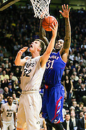 December 7th, 2013:  Colorado Buffaloes senior center Ben Mills (32) attempts to shoot past Kansas Jayhawks redshirt sophomore forward Jamari Traylor (31) during the second half of the NCAA Basketball game between the Kansas Jayhawks and the University of Colorado Buffaloes at the Coors Events Center in Boulder, Colorado