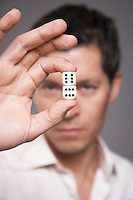 Man holding dice between finger and thumb focus on foreground