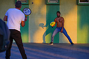 Two young men playing with a paddle and rubber ball AKA Matkot on the beach. Photographed on the beach, Tel Aviv, Israel at sunset