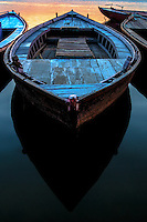 Boat Blue: Weathered wooden boats stand moored during a colourful dawn, with boat tops that express a vibrant blue colour while the boat casts a distinctive deep dark V shaped shadow on the Ganges River, Varanasi India.