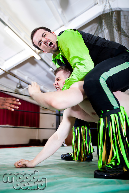 Aggression wrestler giving headlock to rival during match