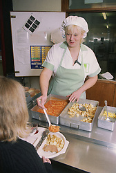 Female refectory assistant serving food to pupil in school canteen,