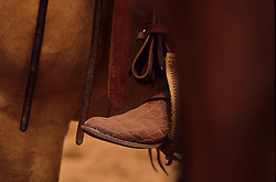 Leather cowboy boot sitting in a saddle stirrup