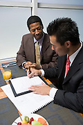 Businessman looking while another businessman signs agreement