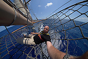 Solvin Zankl photographing on the tall ship Corwith Cramer. Corwith Cramer is a 134-foot steel brigantine built as a research vessel for operation under sail. Sargasso Sea, Bermuda