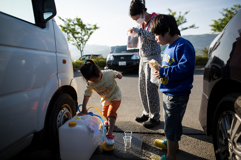 KUMAMOTO, JAPAN - APRIL 20: A family eats bread on early morning on April 20, 2016 in Mashiki Gymnasium parking area, Kumamoto, Japan. As of April 45 people were confirmed dead after strong earthquakes rocked Kyushu Island of Japan. Nearly 11,000 people are reportedly evacuated after the tremors Thursday night at magnitude 6.5 and early Saturday morning at 7.3.<br /> <br /> Photo: Richard Atrero de Guzman