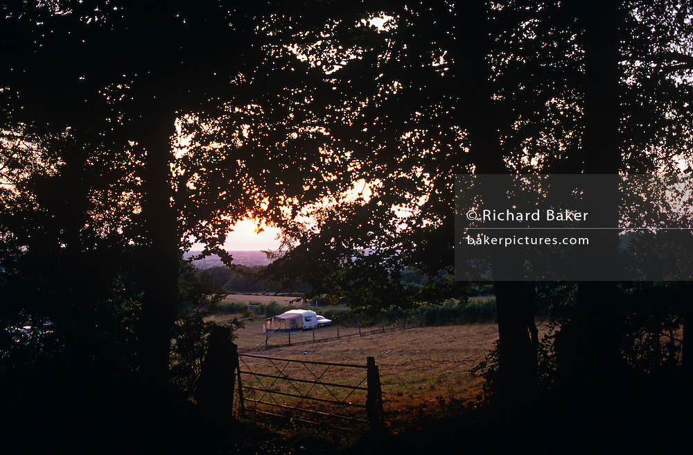 A daylight fades through trees, a lone caravan is pitched in a quiet field overlooking the north Somerset countryside