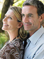 Portrait of couple embracing and smiling outdoors